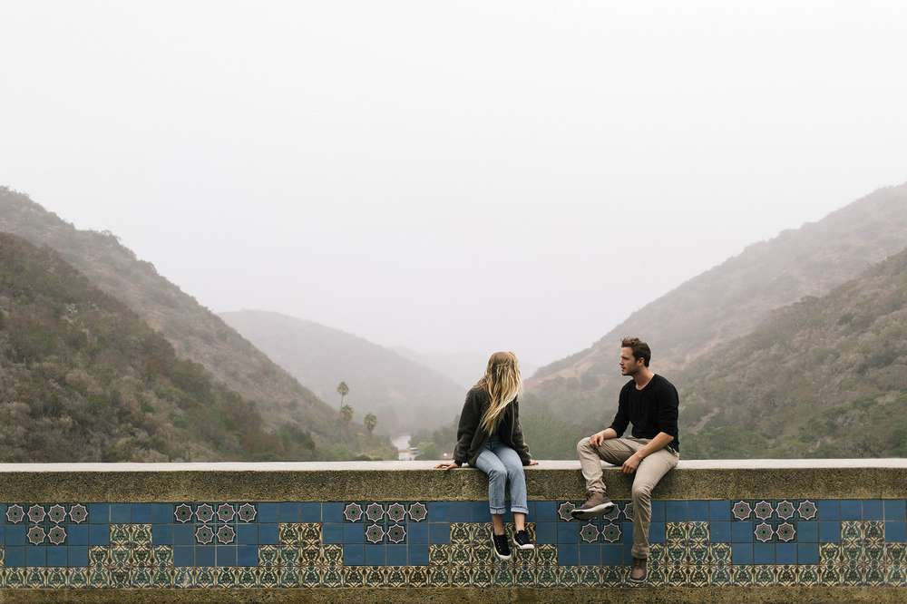 Two friends sit on a ledge overlooking Catalina island wearing Teva shoes.