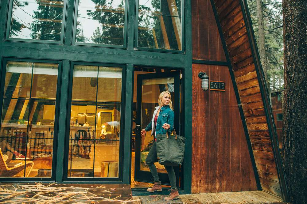 Brooke enters a Tahoe A-frame cabin wearing Teva boots.