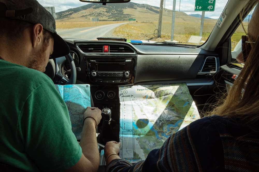 Man pointing at map in car.
