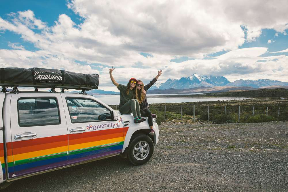 Women sit on hood of Wicked Camper truck in Patagonia
