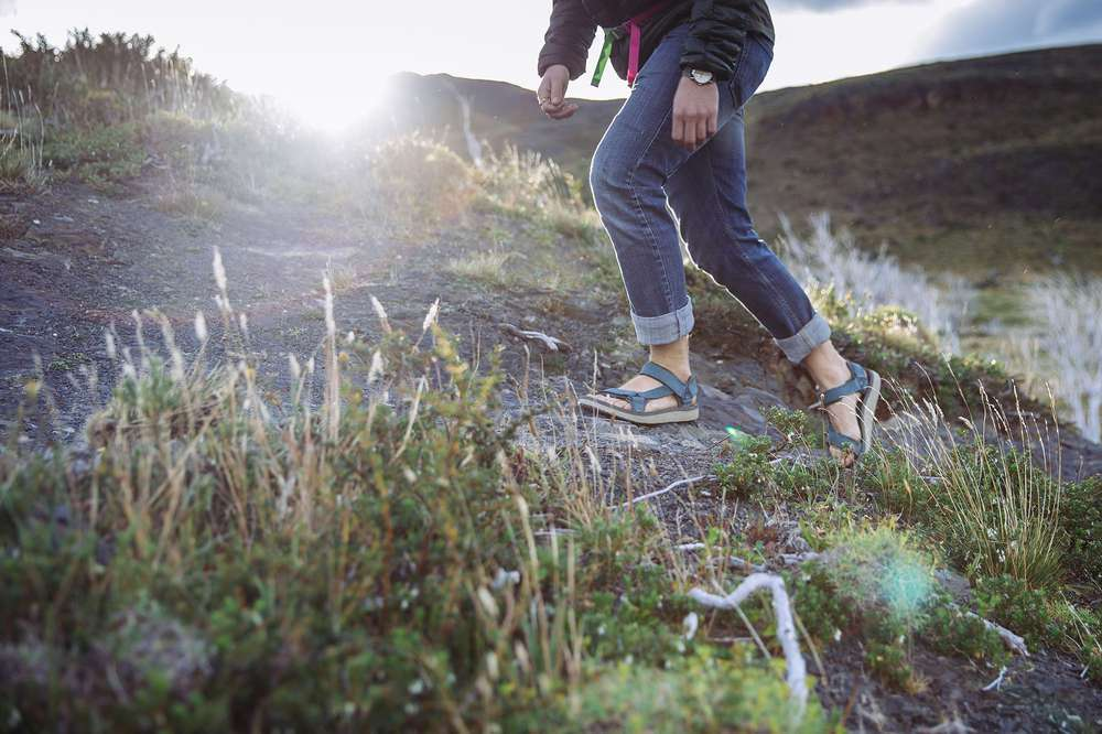 Man walking in field wearing Teva Original Universal Premier Sandal