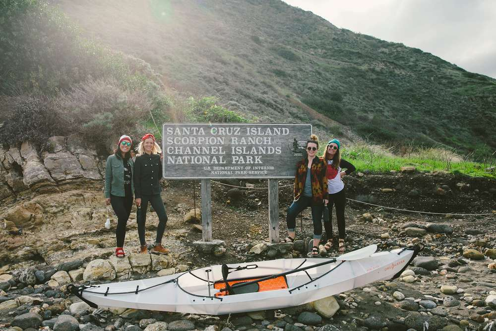 Women posing by sign on Santa Cruz Island with kayaks