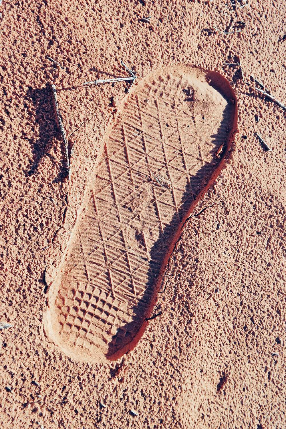 Footprint with Teva logo in desert sand