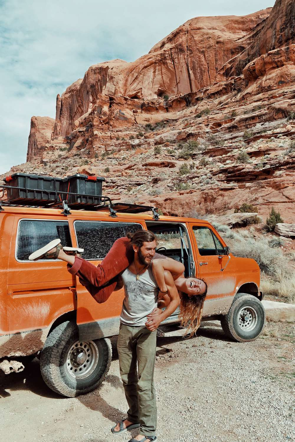 Keith Madia carrying Brianna Madia over should in desert by orange van