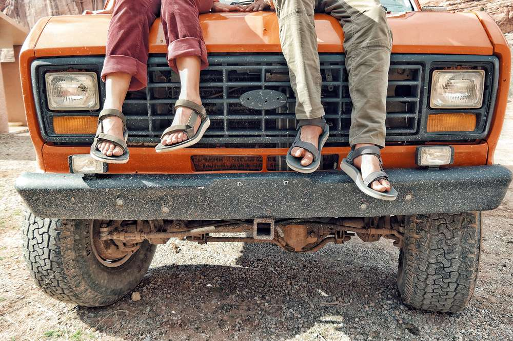 Couples feet dangling on front of van wearing Teva sandals