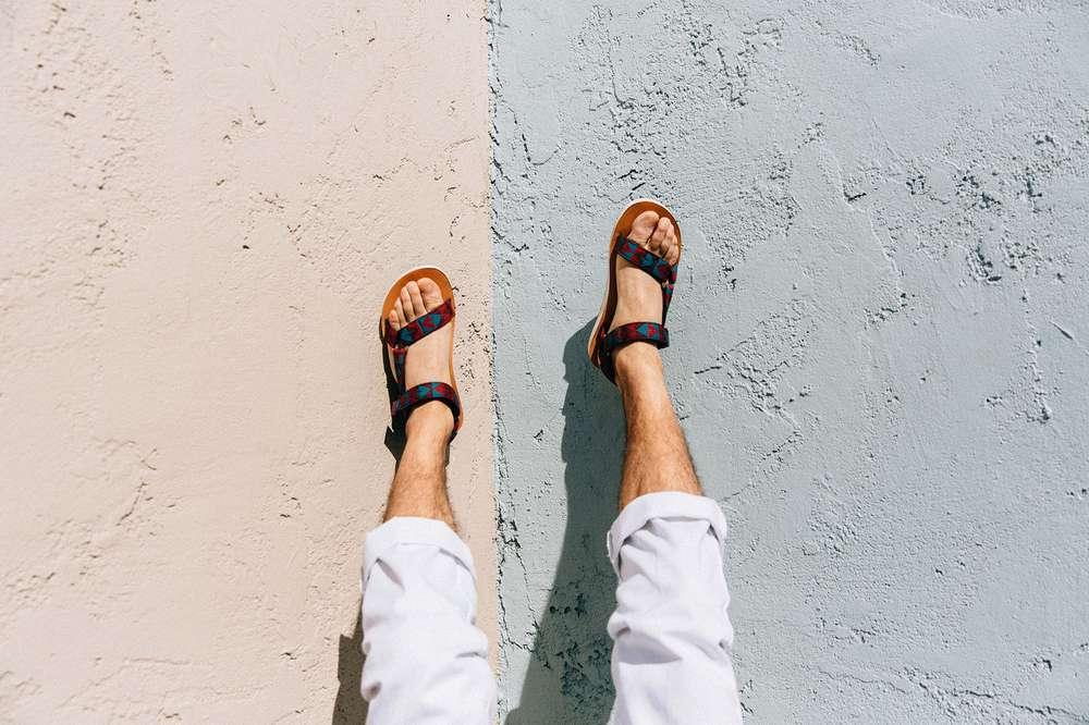 Men's feet against concrete wall wearing Teva sandals