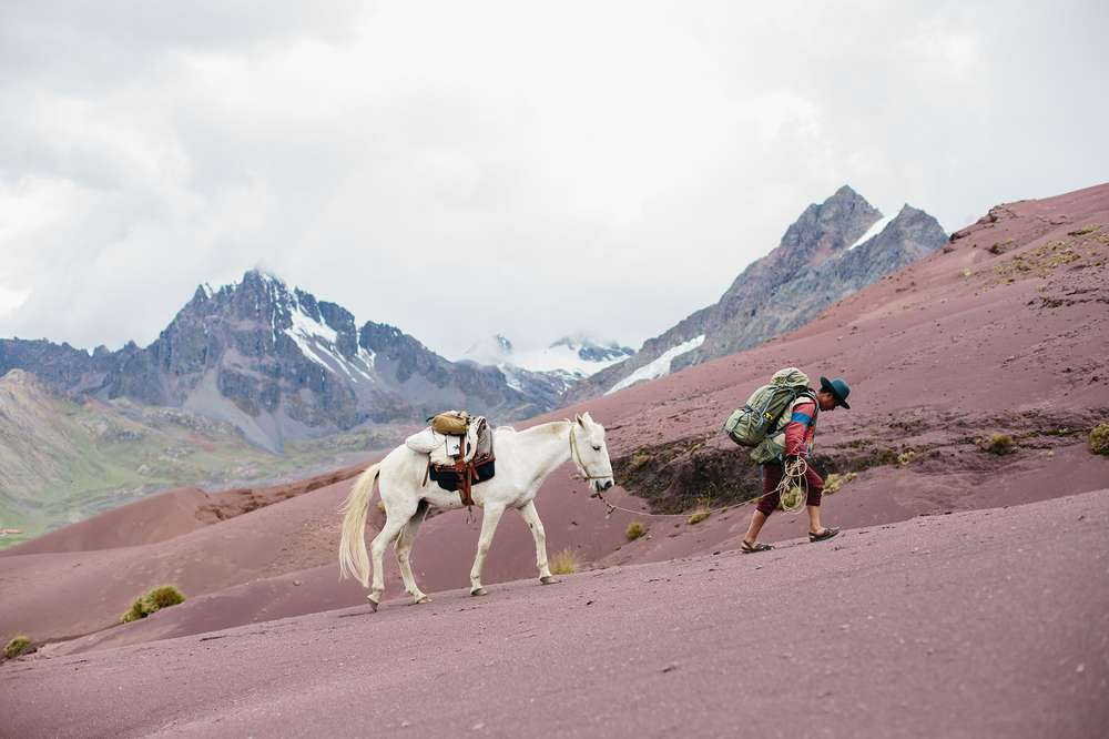 Man walking horse in Andes Peru