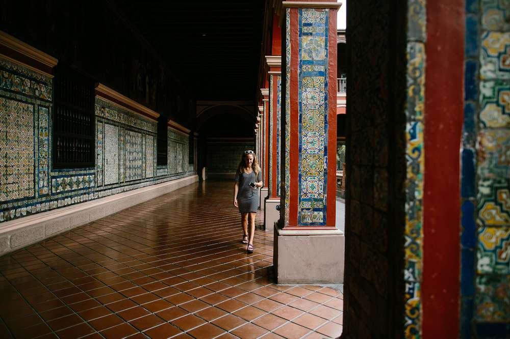 Woman walking by tiled pillars Peru