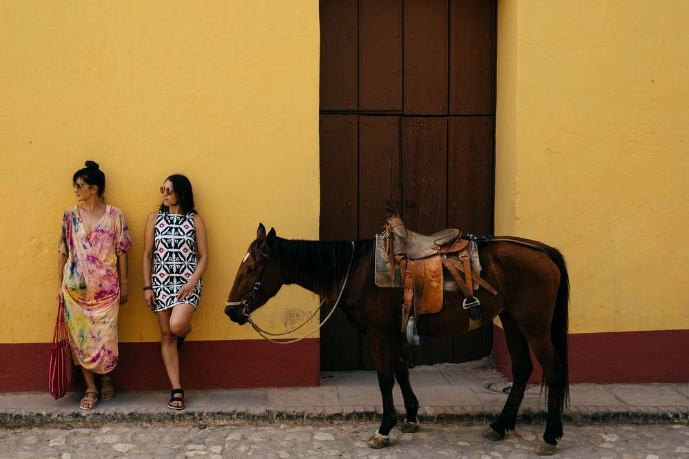 Women stand next to horse on Cuban street