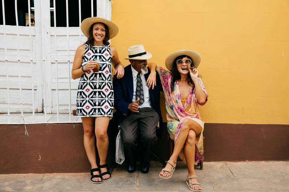 Women laugh next to older man on street in Cuba