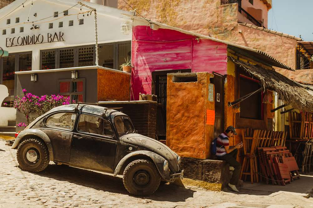 Rusty car parked on colorful street in Sayulita, Mexico