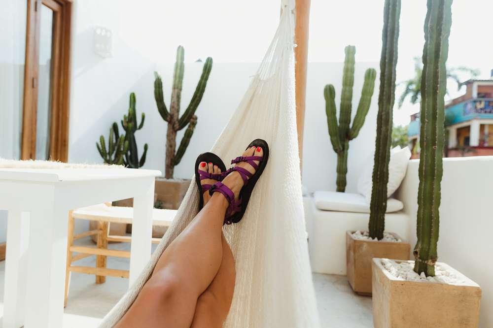Feet in hammock wearing Teva sandals near cacti.