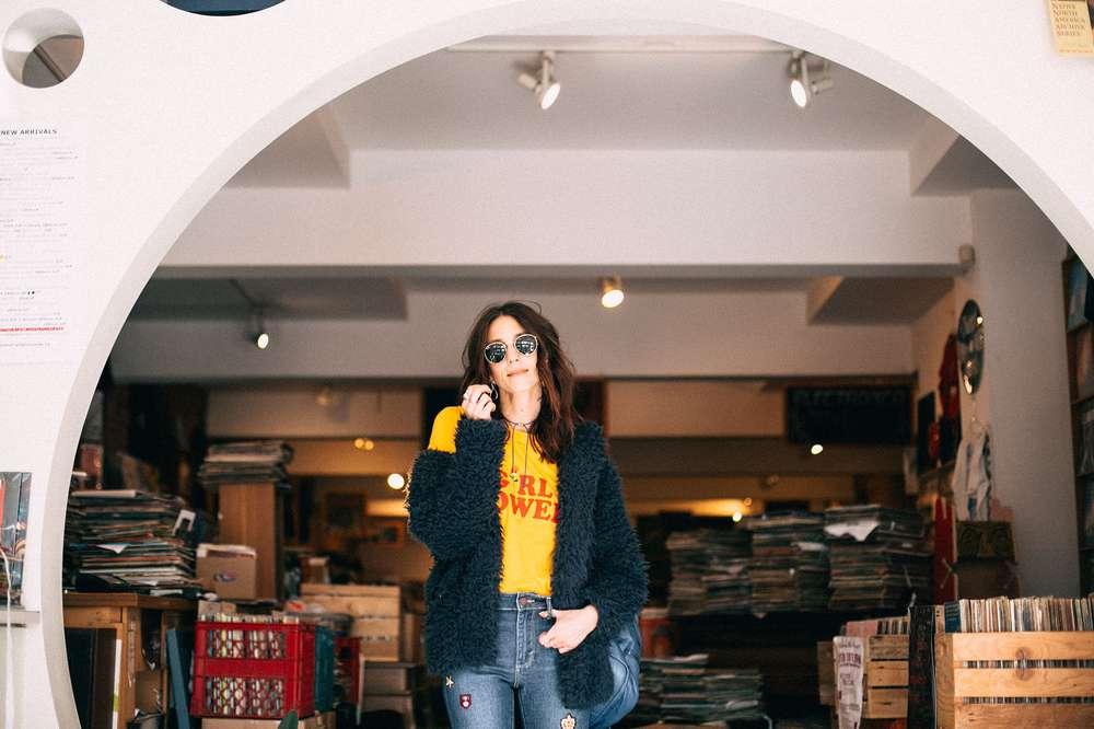 Kiara Schwartz standing by record shop.