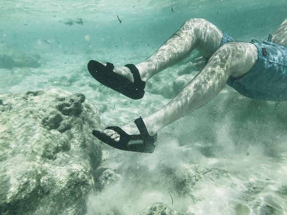 Underwater shot of legs wearing Teva Original Universal sandals