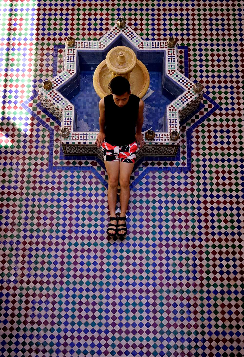 Tommy Lei sitting on tiled fountain in Morocco