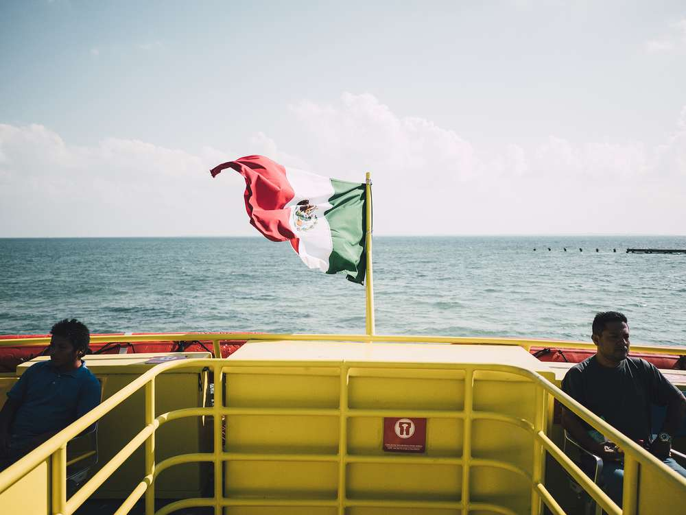 Mexican flag waves on back of yellow boat in ocean