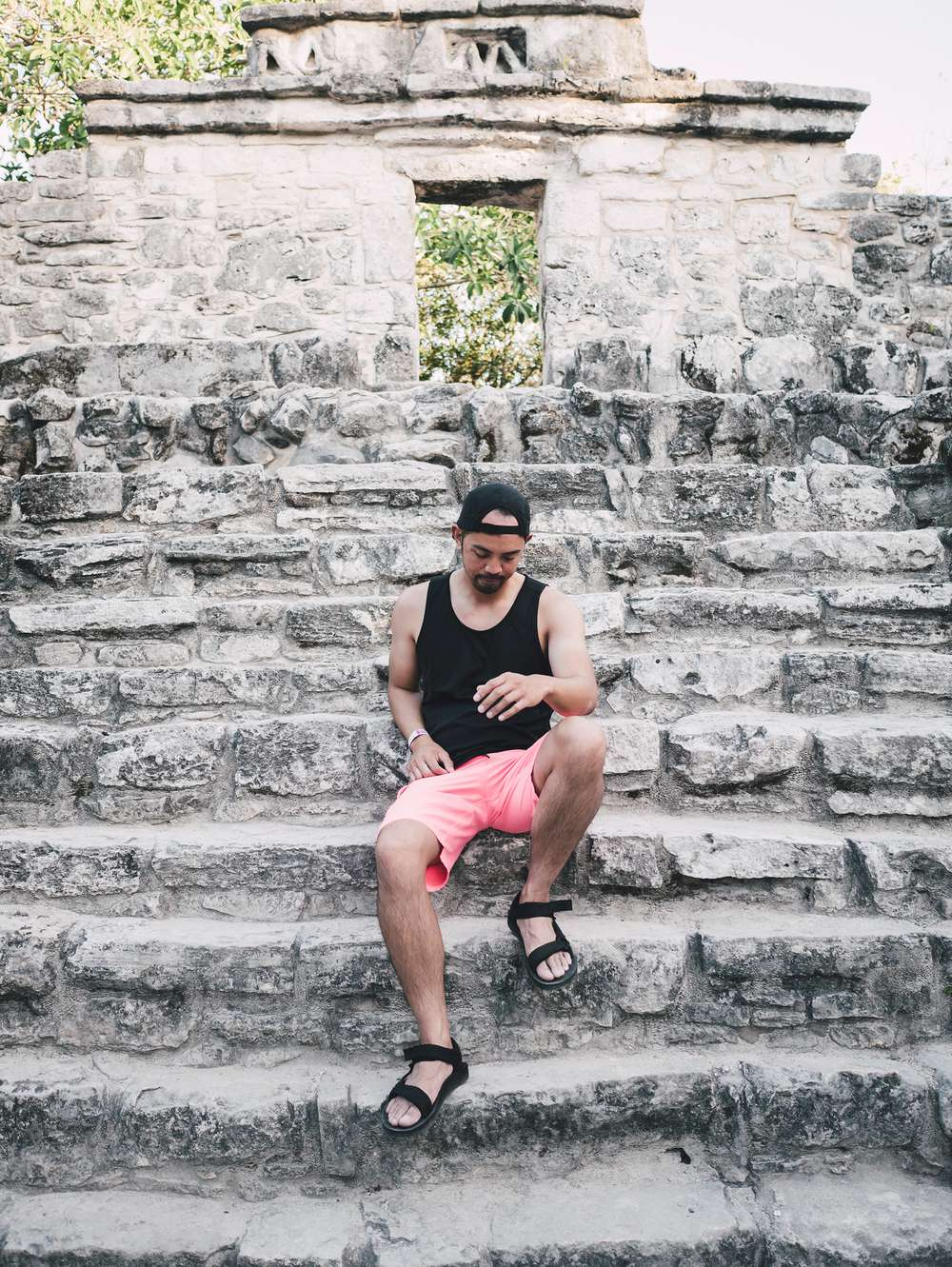 Adrian Narvaez sitting on steps of Mayan ruins