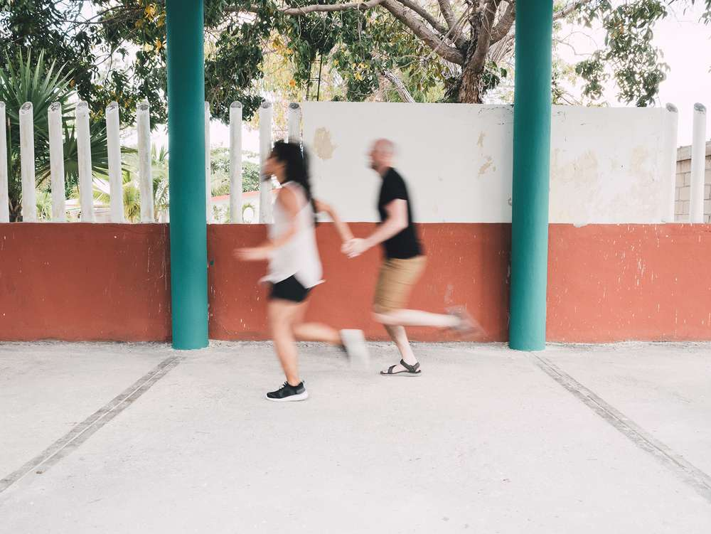 Couple running by colorful wall in Mexico