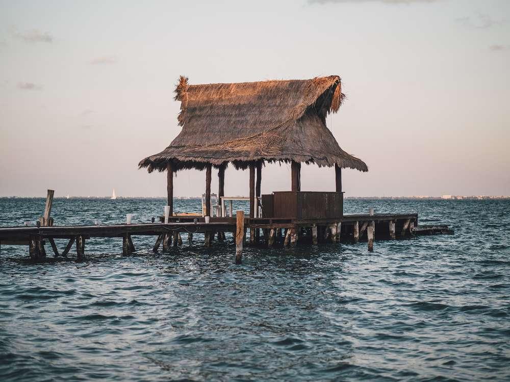 A grass roof hut on pier in ocean.