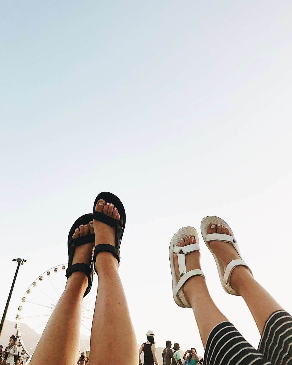Feet in air wearing Teva sandals