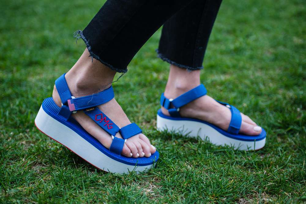 feet wearing embroidered Teva flatform sandals.