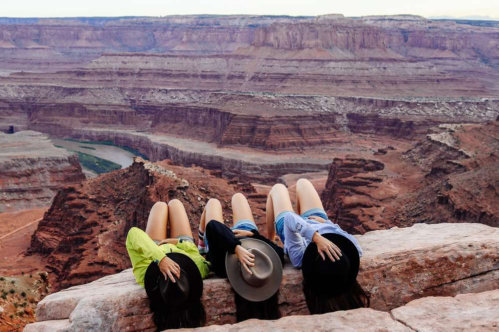 Three sisters in hats on edge of cliff