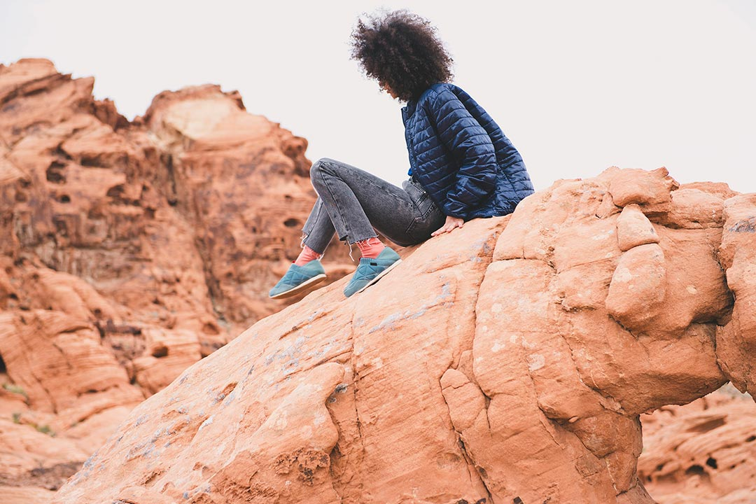 Girl sitting on rocks with Ember Moc shoes.