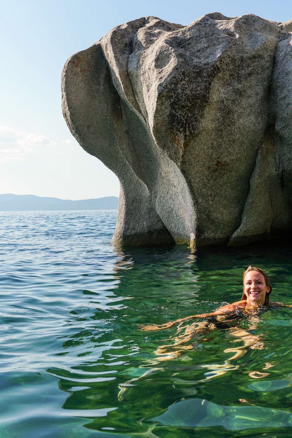 Photo of woman swimming by boulder in Lake Tahoe
