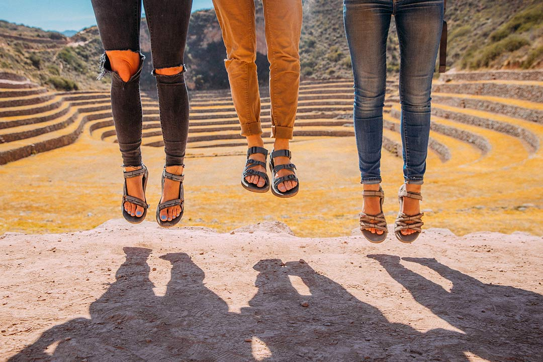 Three pairs of feet jumping wearing Teva sandals