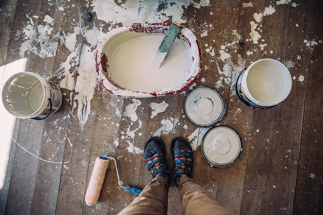 Feet next to buckets of paint