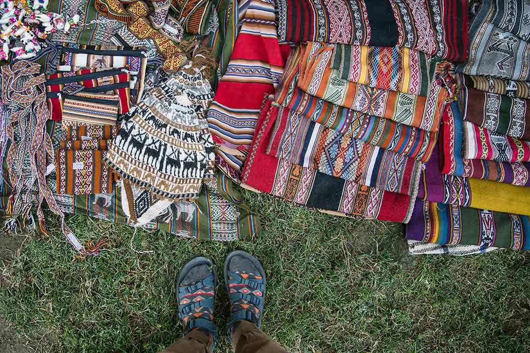 Feet next to a pile of textiles.