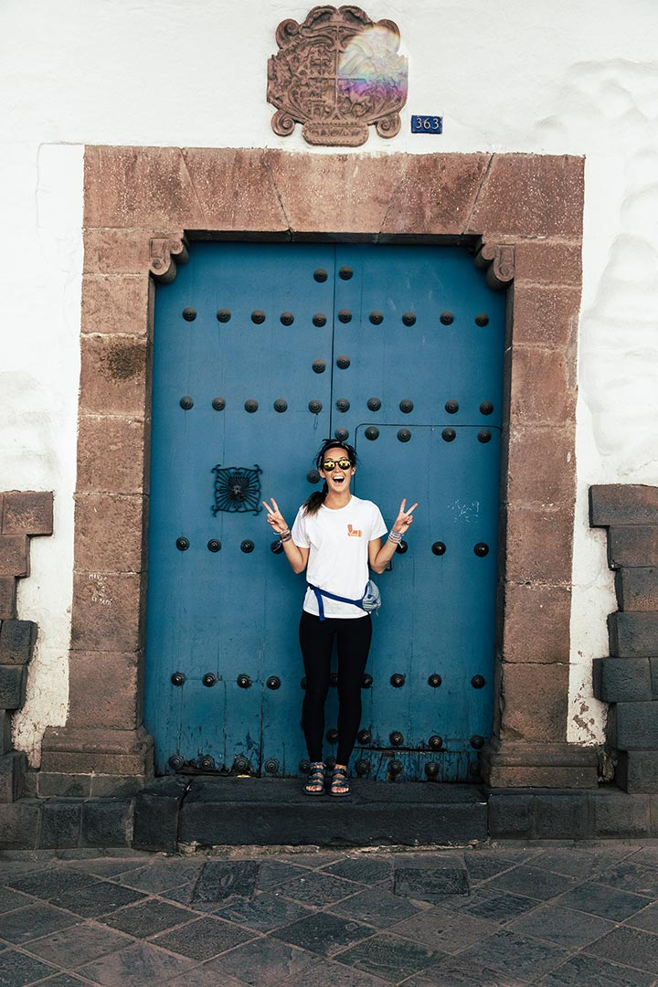 Woman standing in front of blue door.