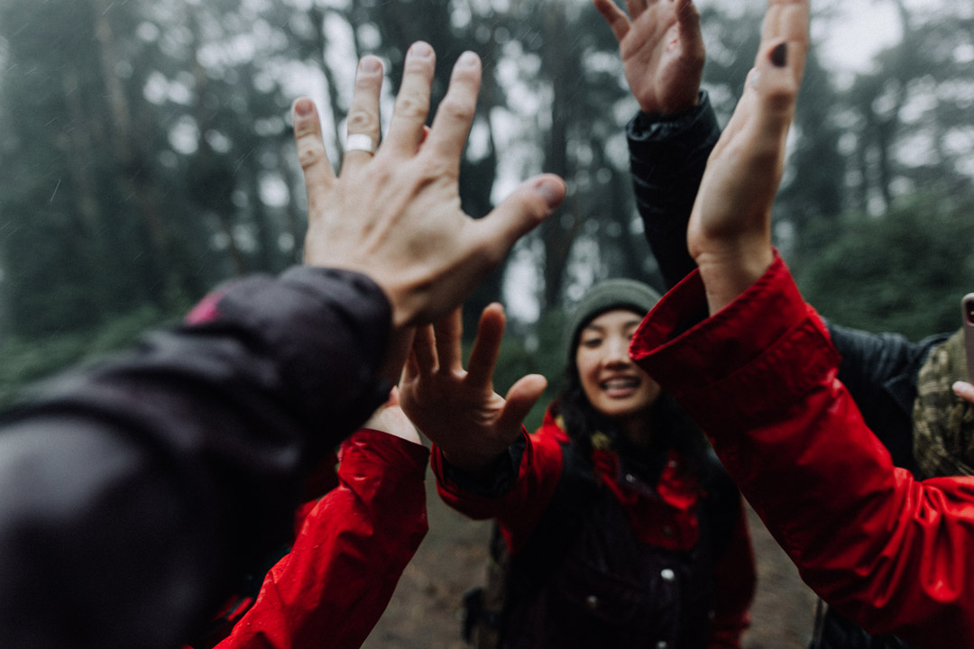 A group of hikers giving high fives.