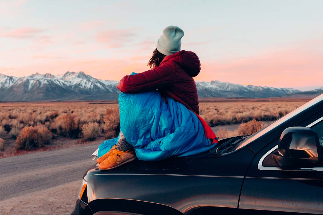 woman sits on hood of car by mountains