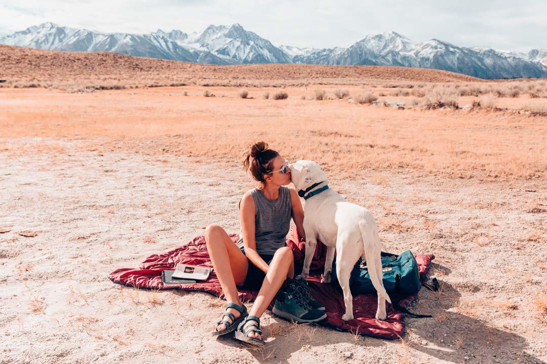 Woman kisses her dog in desert.