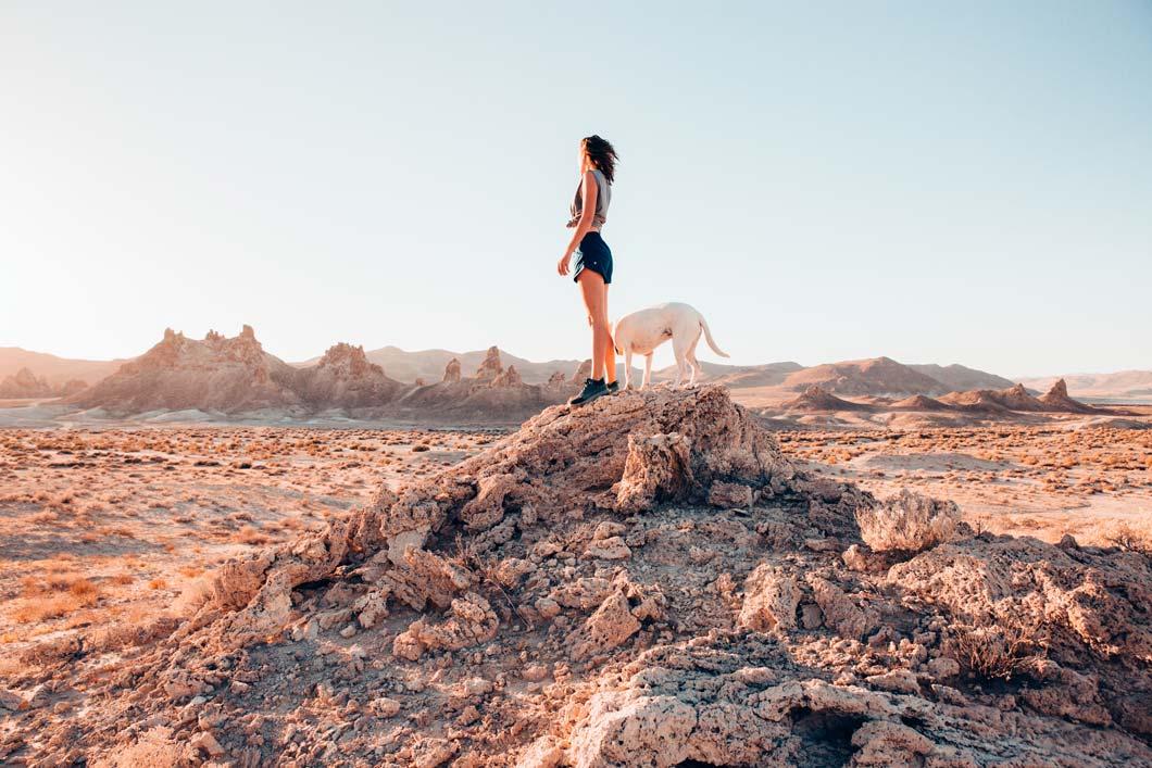 Woman and dog standing on rocks.