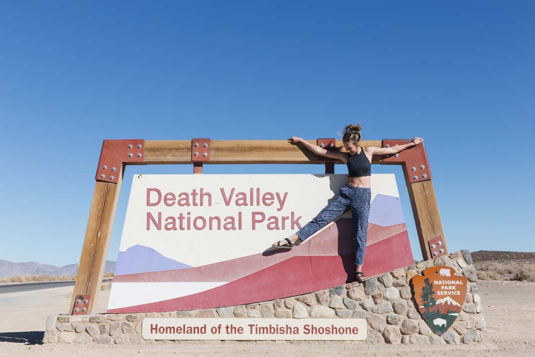 Teva blog editor Johnie Gall stands on the sign for Death Valley National Park in California while wearing the Teva Original Universal in Black.