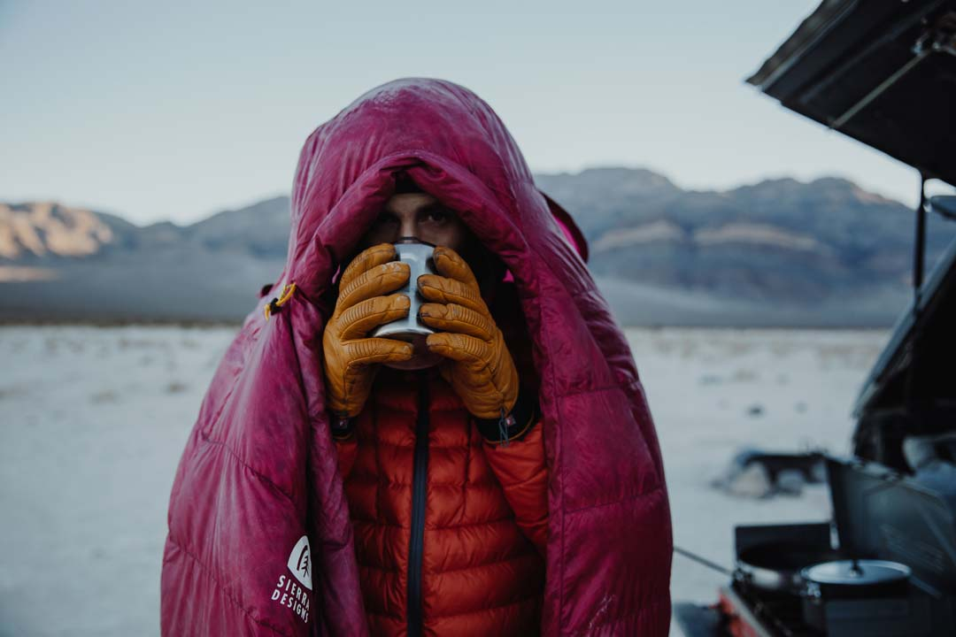 Teva Explorer Andy Cochrane sips coffee from a stainless steel tumbler while wrapped in a down sleeping bag on a cold morning in Death Valley National Park.
