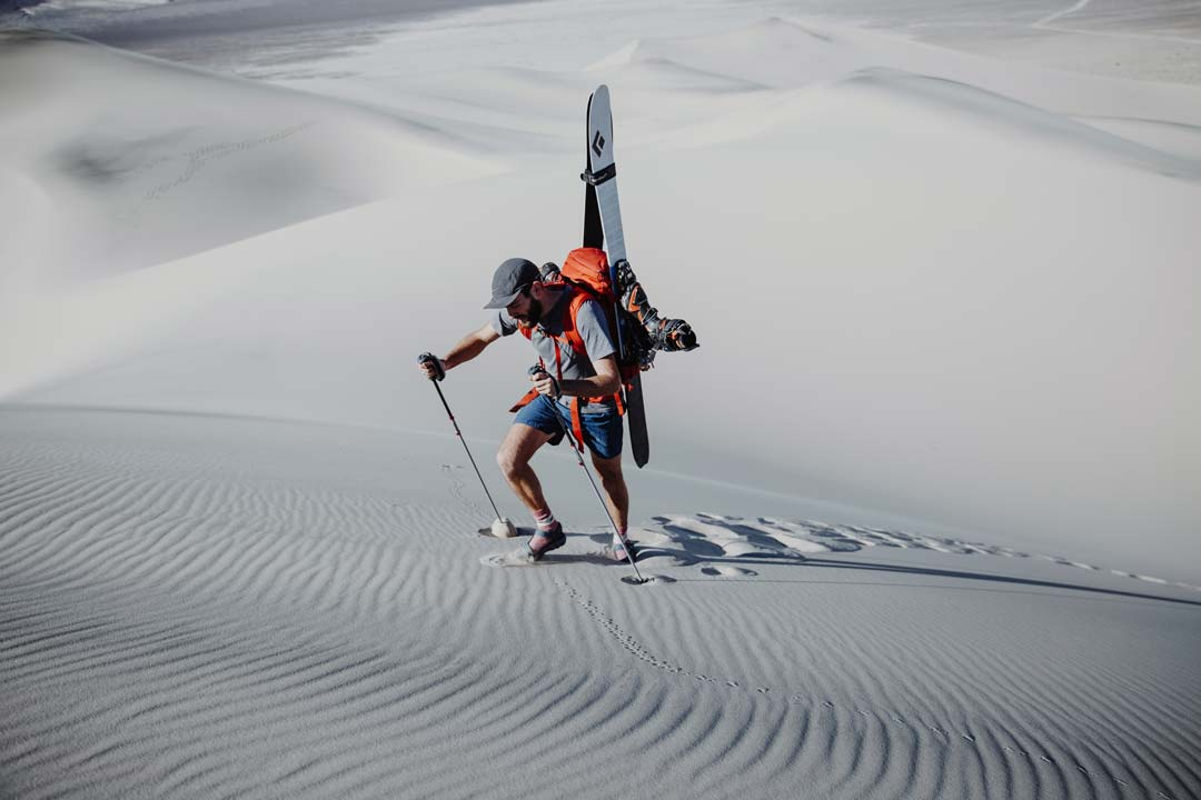 Teva Explorer Andy Cochrane climbs a sand dune in Death Valley National Park with skiis on his backpack. He wears socks and Teva Hurricane XLT sandals.