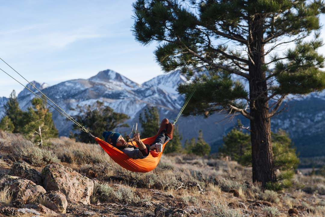 Andy Cochrane relaxes in a red hammok at his campsite off the 395 highway near Mammoth, California. He wears the Teva Ember Moc in Picante.