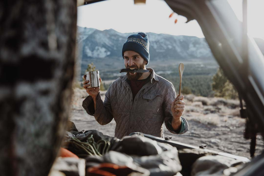 Andy Cochrane holds cooking utensils and a knife in his mouth as he prepares dinner at a campsite from the back of his truck.