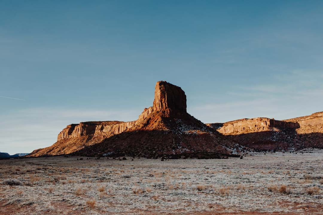 A red rock tower rises out of Bears Ears National Monument during sunrise against a blue sky.