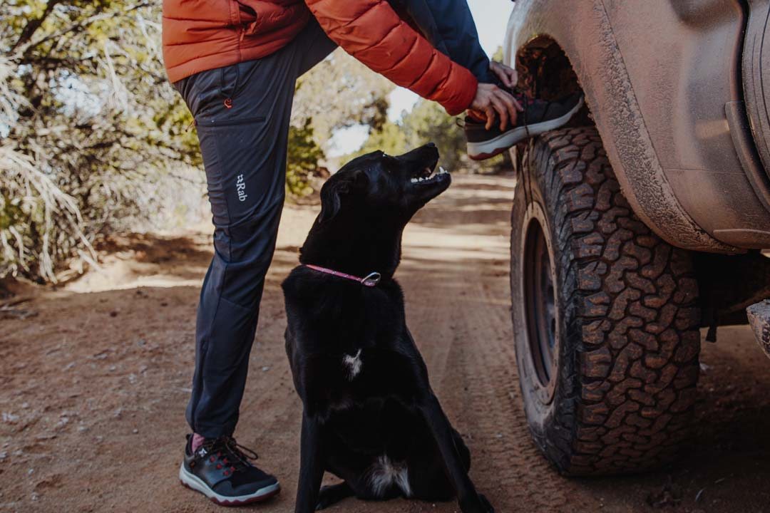 Andy Cochrane ties his shoes on a truck tire next to his black dog, Bea. He wears the Men's Arrowood waterproof sneakerboots.