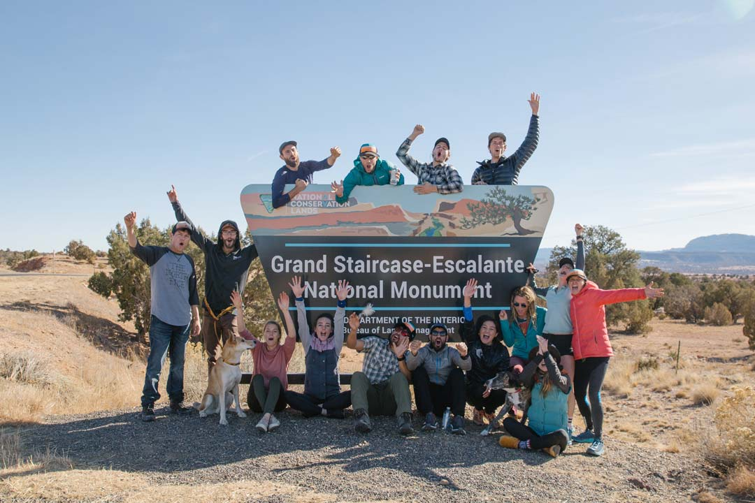 Andy Cochrane an a group of runners celebrate next to the official sign for Grand Staircase-Escalante National Monument after running 250 miles across Bears Ears and Grand Staircase in a single weekend.