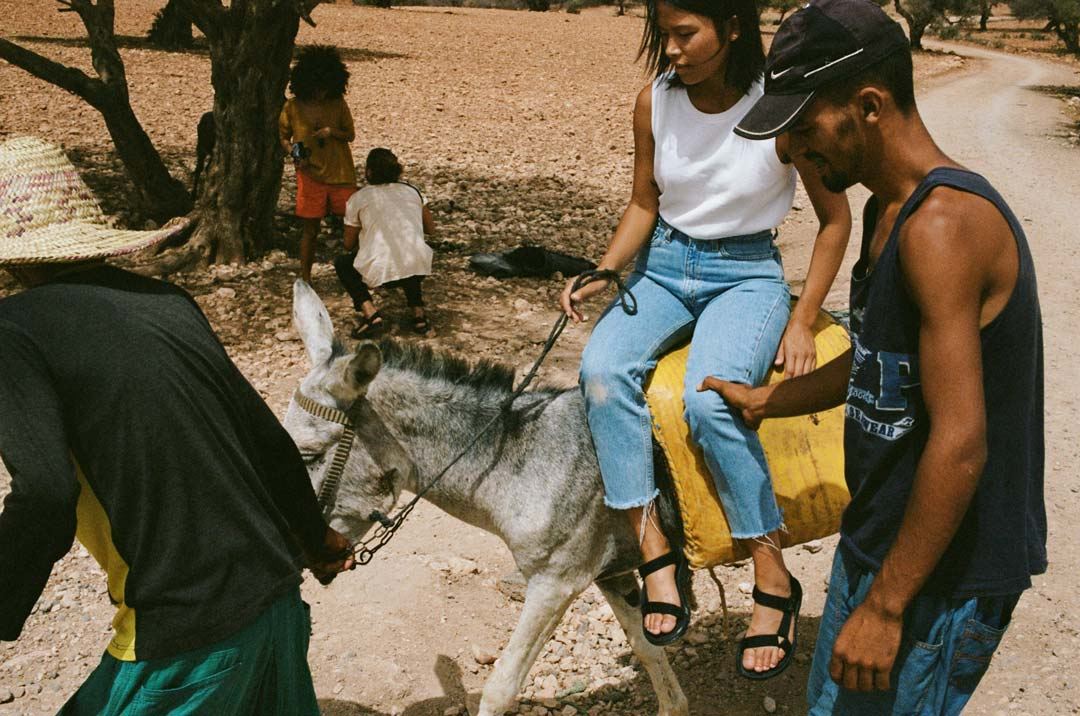 Maly Mann rides a donkey in Morocco wearing Teva Original Universal sandals.