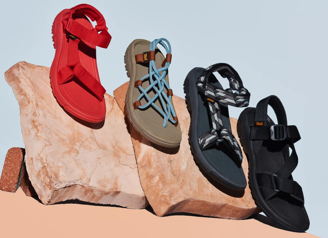 The Teva Hurricane XLT2 collection posed on rocks in a studio.