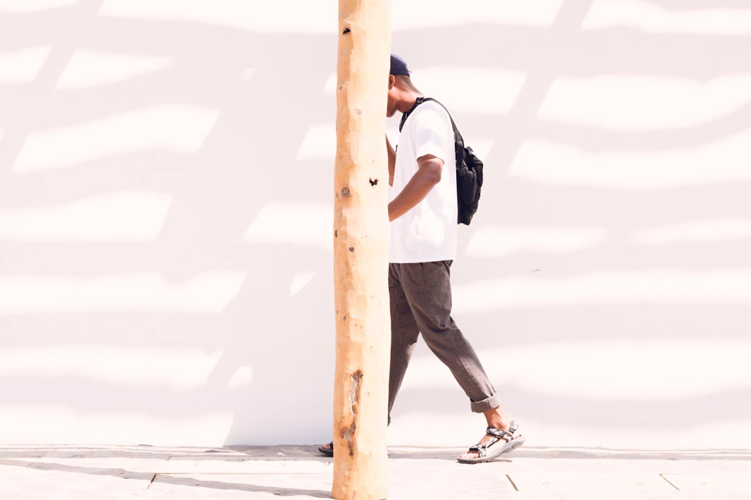 A man walking behind a tree by a concrete wall wearing the Hurricane XLT2
