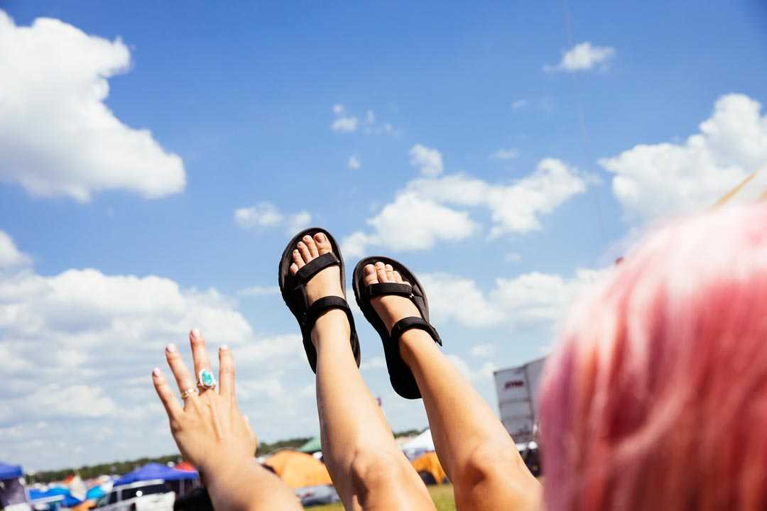 Woman with her feet up in the air wearing Teva Original Universal sandals.