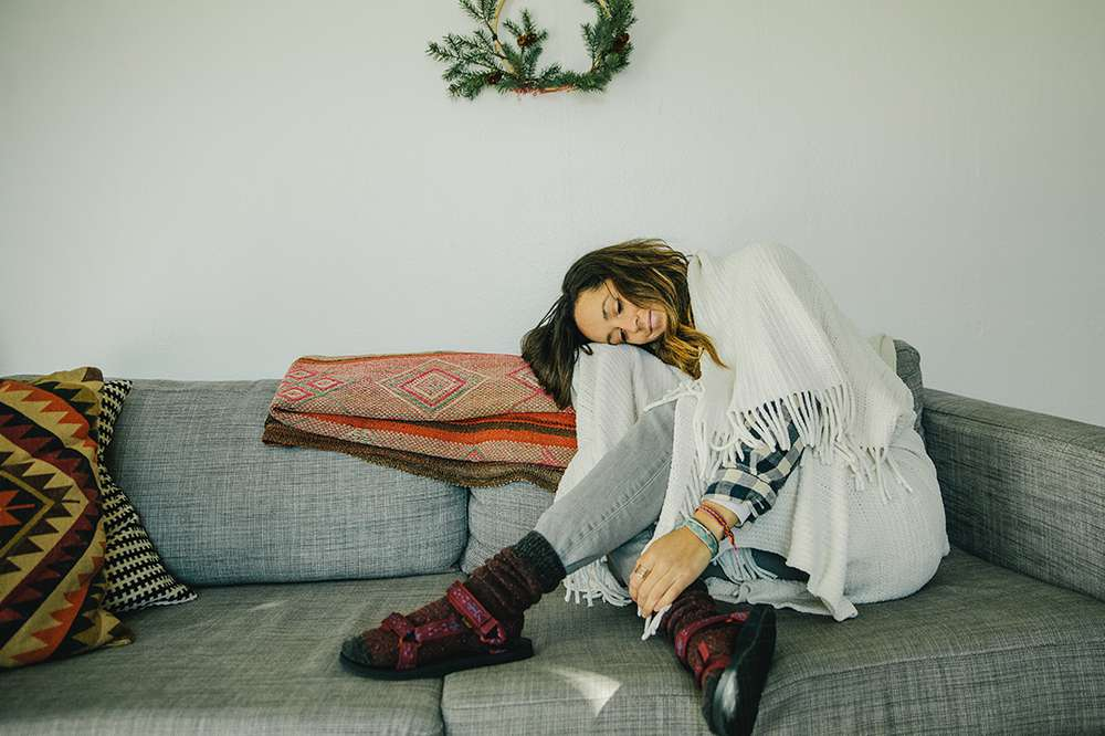 Photographer Kylie Fly wears Teva sandals and socks while relaxing at home during the holidays.