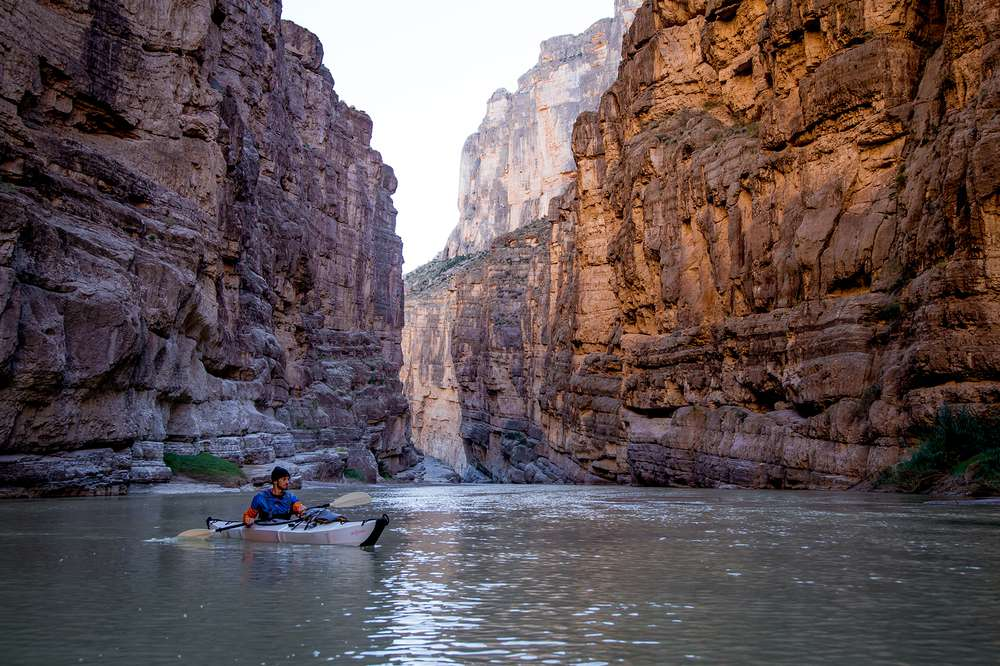 A kayaker looks at the towering walls of the Santa Elena Canyon in Big Bend National Park.